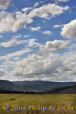 View near Barrington Tops showing the blue haize of the Eucalyptus trees on the mountains and the gathering storm clouds in the sky.