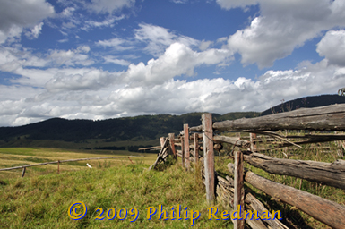 Shot across a splintered hardwood fence with surrounding mountains and masses of fluffy white clouds.