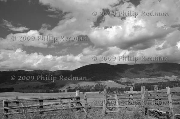 Black and white image of an old hardwood fence on property near Barrington Tops with view of the hills and masses of cloud in background.