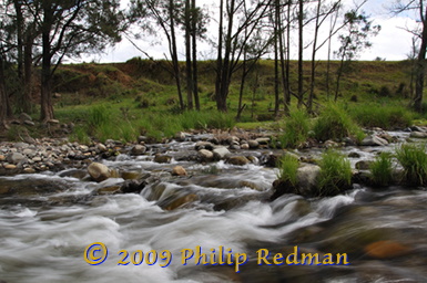 Fast flowing water down a pebbled riverbed.